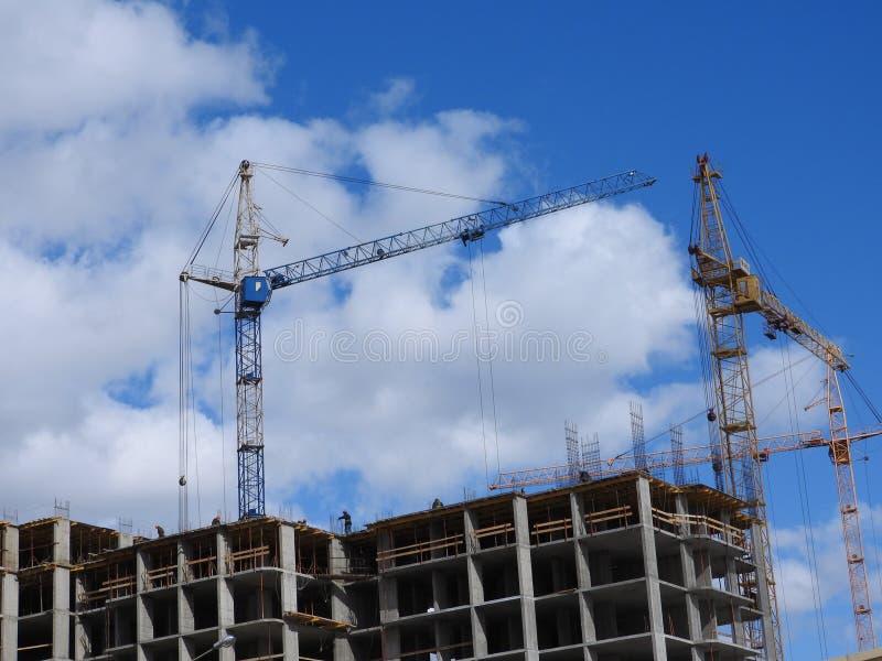 大工地工作,包括运转在建筑复合体的几台起重机,与一清楚的天空蔚蓝 免版税库存图片