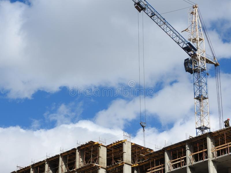 大工地工作,包括运转在建筑复合体的几台起重机,与一清楚的天空蔚蓝 免版税库存照片