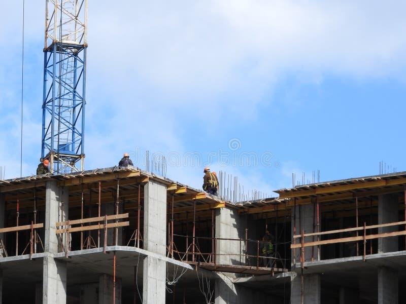大工地工作,包括运转在建筑复合体的几台起重机,与一清楚的天空蔚蓝 库存图片