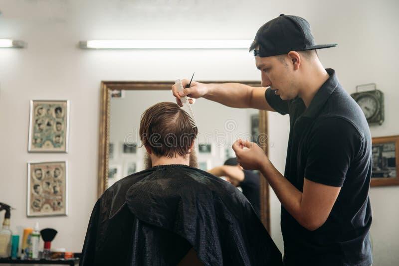 大师剪头发,并且人在理发店,美发师胡子做一个年轻人的发型 免版税图库摄影