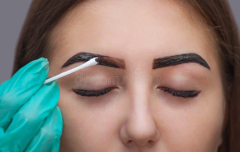 大师改正构成,它给形状并且上色眼眉在美容院的无刺指甲花,温泉 库存照片