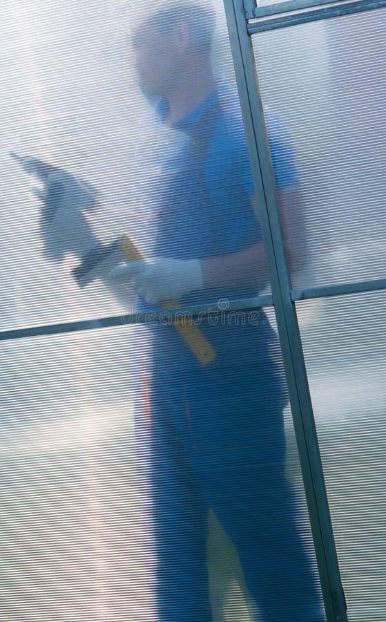 大师运作作为一把螺丝刀,在聚碳酸酯纤维的另一边,他的阴影是可看见的 免版税库存照片