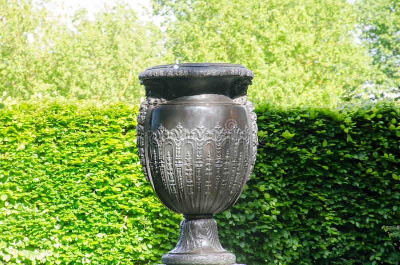 大希腊样式花瓶在有树篱的规则式园林里 免版税库存图片