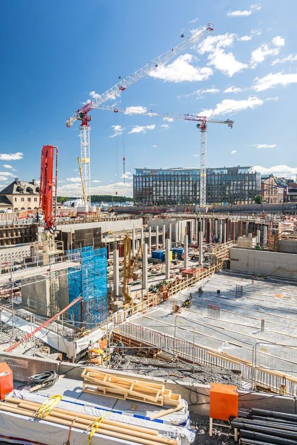 大建筑工地在与起重机和基础的市区 免版税库存图片