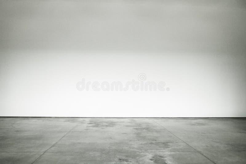 大开放室优美的水泥地板和墙壁被绘白色 免版税库存图片