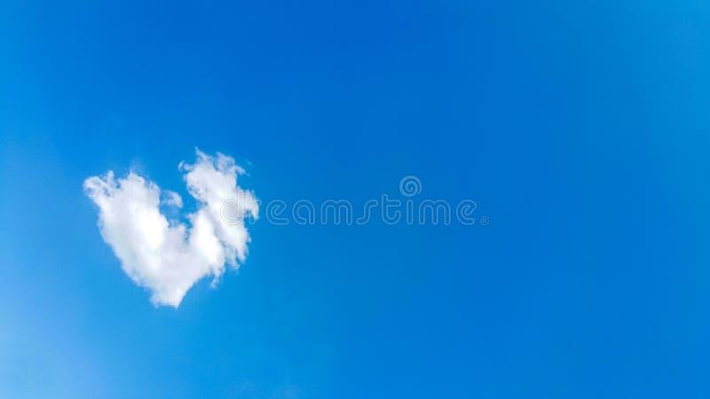 大心形的云彩,爱题材的美好的背景,明显地看白色云彩和天空蔚蓝线在太阳上 免版税库存照片