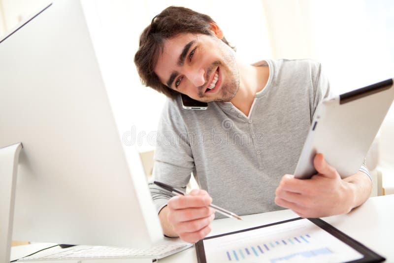 年轻大忙人在使用片剂和智能手机的办公室 免版税库存图片