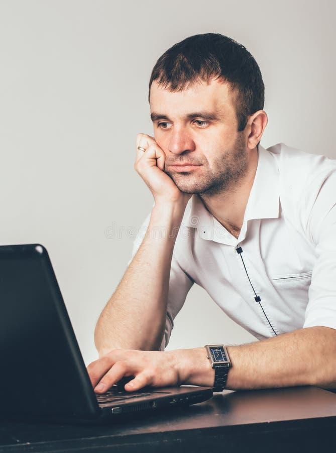 大忙人坐在膝上型计算机在屋子里 在白色衬衫的商人有黑垂直的小条工作的在办公室 免版税库存照片