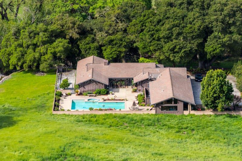 大房子鸟瞰图有树和绿色草甸围拢的水池的,圣荷西,圣塔克拉拉县,南部旧金山湾 图库摄影