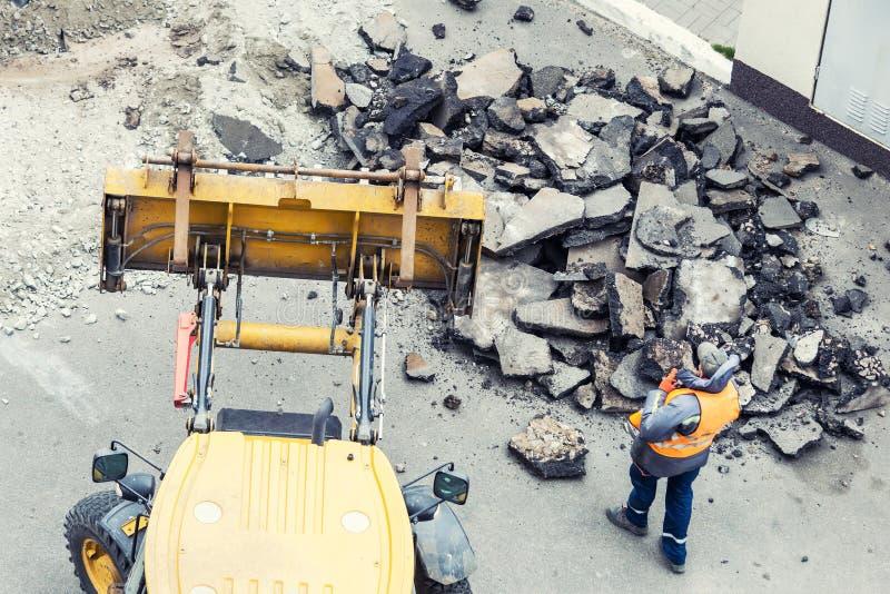 大手提凿岩机钻子钻井路 击碎暴雨水流失修理的大量手段沥青 库存照片