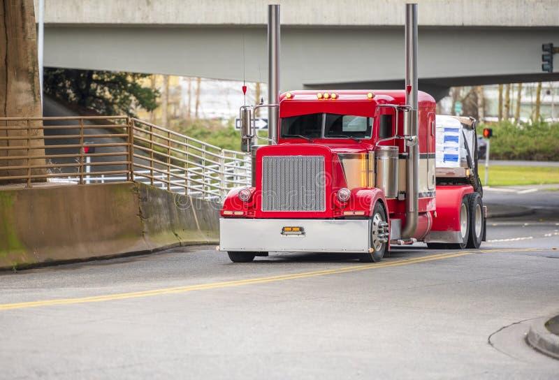 大持久溃败的半船具明亮的红色经典美国偶象卡车与运输半拖车的高镀铬物排气管 免版税图库摄影