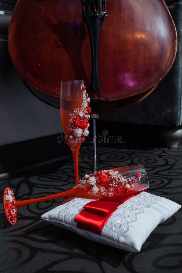 大提琴和两个红色葡萄酒杯在枕头 免版税库存图片
