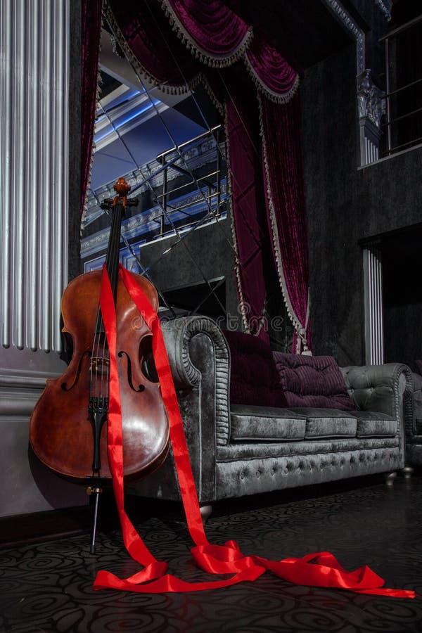 大提琴和红色丝带在灰色长沙发 库存照片
