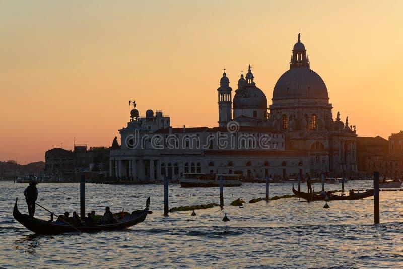 大教堂二圣玛丽亚della致敬和运河重创在日落在威尼斯 免版税库存照片