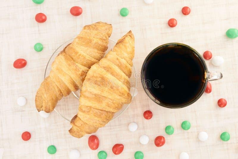 大新月形面包 热茶 多彩多姿的糖果 库存图片