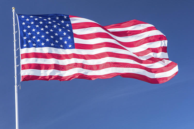 大旗子美国美国担任主角有风条纹杆的蓝天 免版税图库摄影