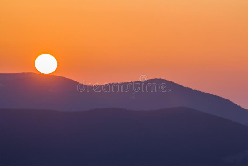大明亮的白色太阳意想不到的宽全景视图在剧烈的橙色天空的在日落或日出的黑暗的紫金山范围我 免版税图库摄影