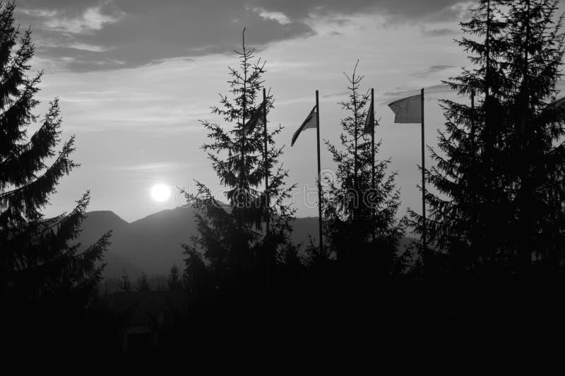 大明亮的白色太阳看法在剧烈的橙色天空的在日落的黑暗的在山的山脉或日出 r 免版税库存图片