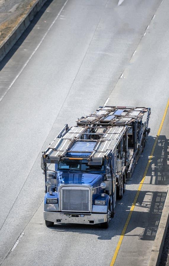 大有运行在路的空的拖车的船具蓝色半半汽车搬运工卡车为装载的汽车储藏 免版税库存图片
