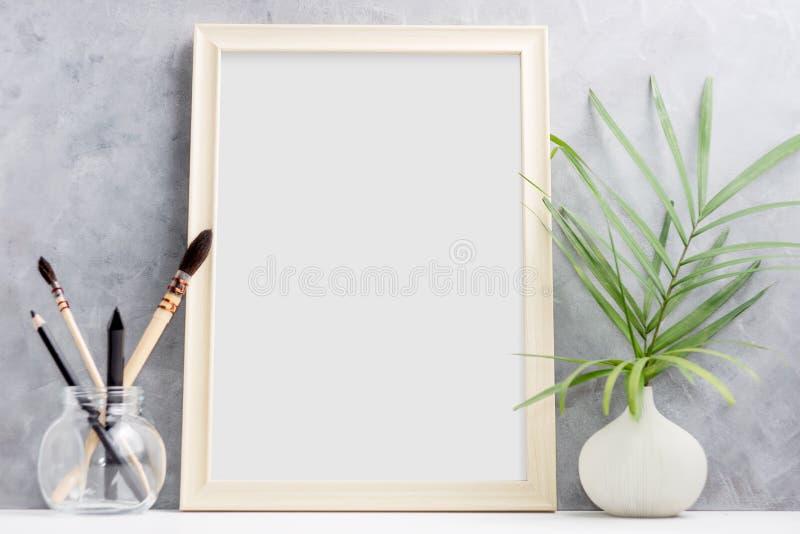 大木照片框架嘲笑与在花瓶的绿色在玻璃的棕榈叶和刷子在架子 斯堪的纳维亚样式 库存照片