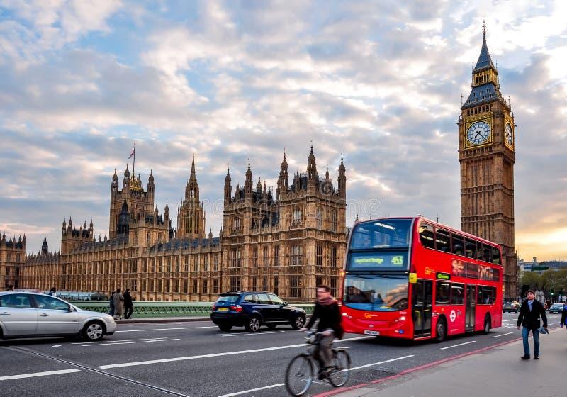 大本钟和双层汽车在威斯敏斯特桥梁在日落,伦敦,英国 免版税库存照片