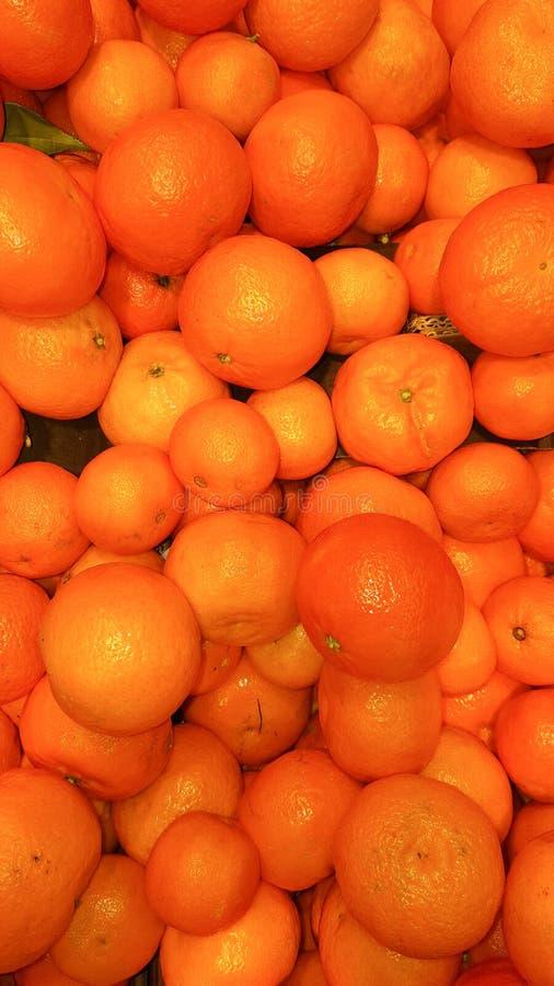 大束成熟蜜桔桔子作为在市场摊位的背景 免版税库存图片