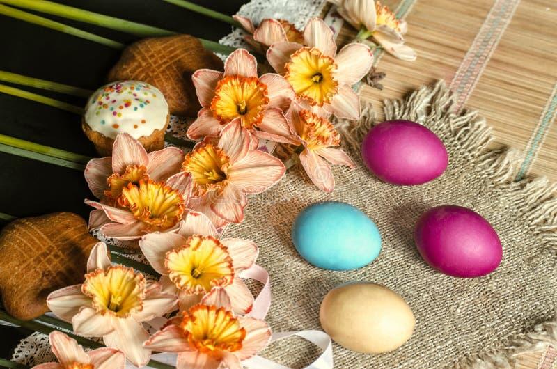 大桃红色黄水仙和饼干在粗麻布用被绘的复活节彩蛋在秸杆地毯说谎 免版税库存图片