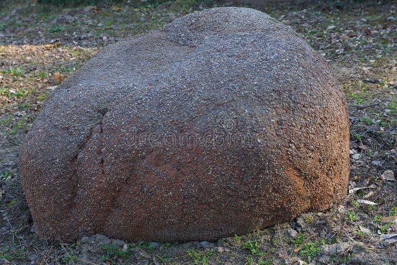 大棕色石头说谎在草和在地面上本质上 图库摄影