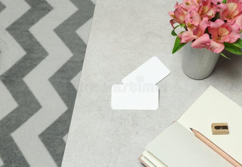 大模型在花岗岩桌上的名片与笔记和花 图库摄影