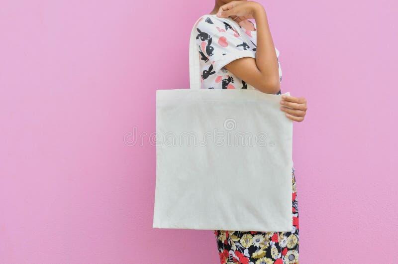 大模型女孩拿着空白的棉花袋子 手工制造eco购物 库存图片
