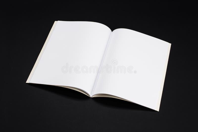 大模型杂志、书或者编目在黑桌背景 免版税库存照片