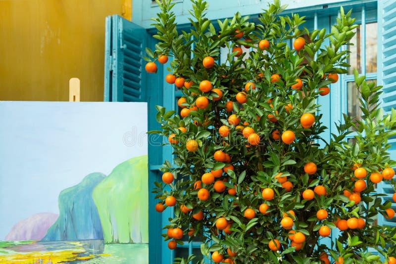 大橘树用成熟和新鲜水果和近水彩的绘画染黄有蓝色快门的房子 免版税库存图片