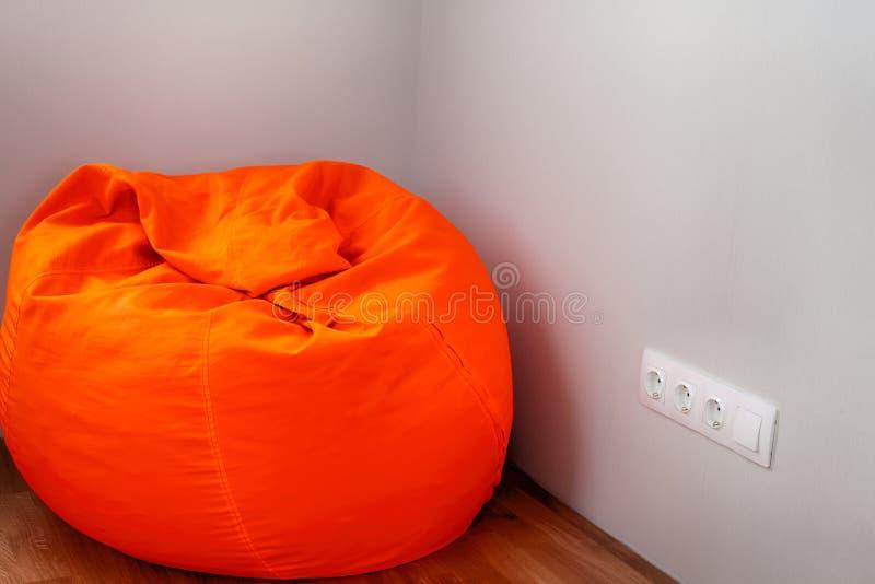 大橙色装豆子小布袋在屋子角落里 免版税库存图片