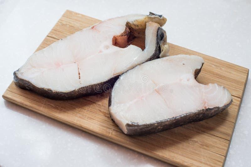 大比目鱼在一块砧板的鱼排 图库摄影