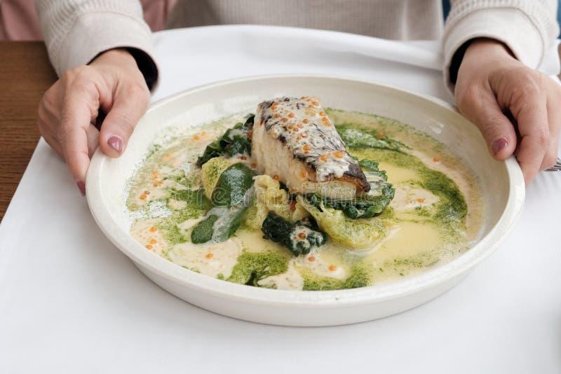 大比目鱼鱼烹调在一块白色板材的用在框架的手 免版税库存照片
