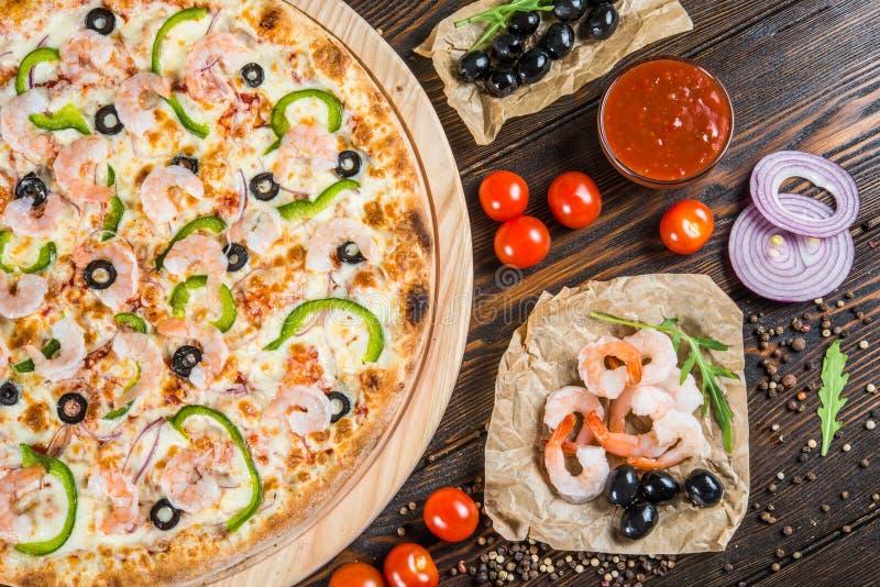 大比萨用海鲜、虾和黑橄榄在一圆的cutt 库存照片