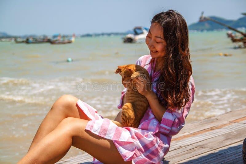 大气年轻美丽的亚裔妇女生活方式坦率的照片假期戏剧的与猫 免版税图库摄影