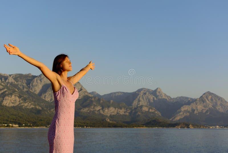 大气照片 一个美丽的少妇站立与在一个夏天伸出的她的胳膊sarafan 地中海和高 免版税图库摄影
