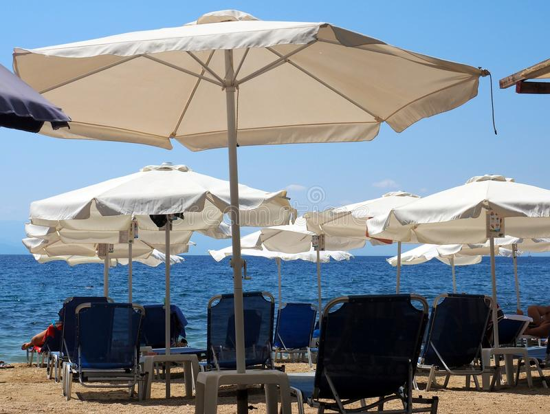 大沙滩伞和椅子在希腊海滩 免版税库存照片