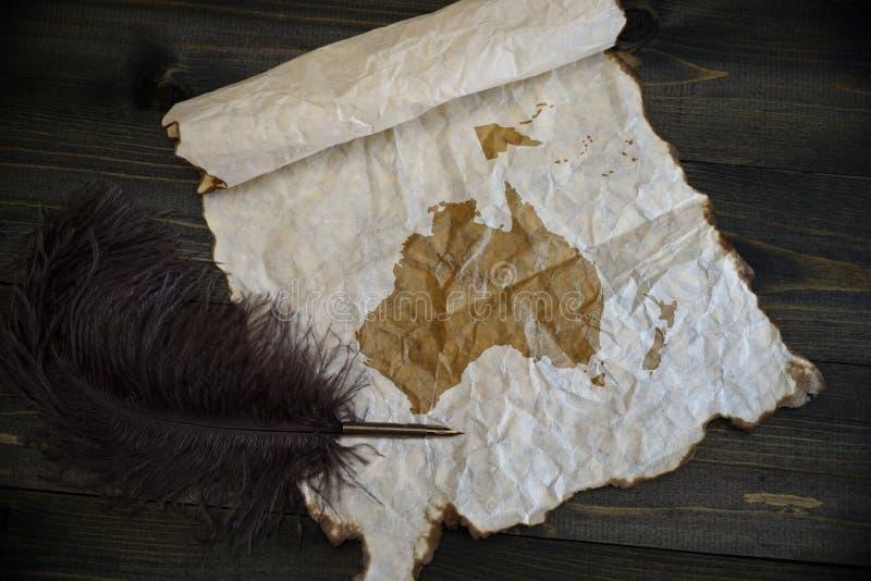 大洋洲地图葡萄酒纸的与在木纹理书桌上的老笔 免版税图库摄影