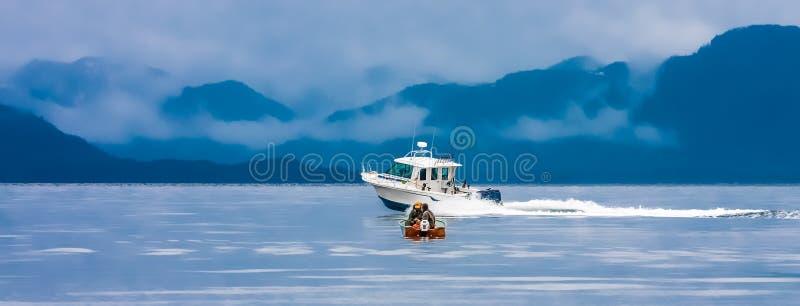 大渔船通过的小渔船 库存照片