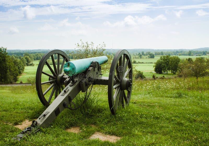 大炮坐俯视谷的小山顶 免版税库存照片