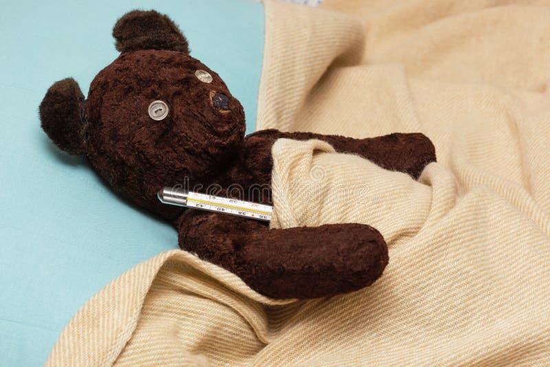 大熊玩具是病与流行性感冒,测量温度  图库摄影
