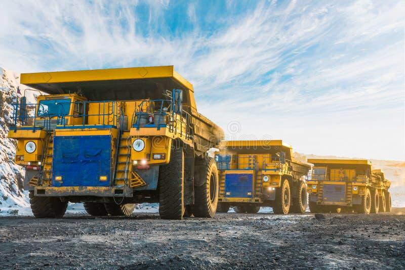 大猎物翻斗车 装载岩石在倾销者 装货煤炭到身体卡车里 生产有用的矿物 开采 免版税库存图片