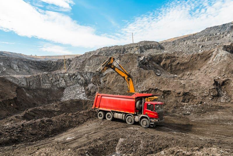 大猎物翻斗车 装载岩石在倾销者 装货煤炭到身体卡车里 生产有用的矿物 开采 免版税图库摄影
