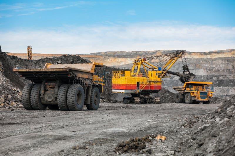 大猎物翻斗车 装载岩石在倾销者 装货煤炭到身体卡车里 生产有用的矿物 开采 免版税库存照片
