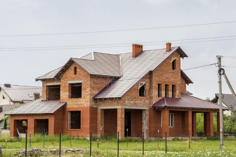 大现代两层没有完成了有陡峭的棕色盖的屋顶的,车库,在蓝色的高烟囱新的砖家庭村庄房子 免版税库存图片