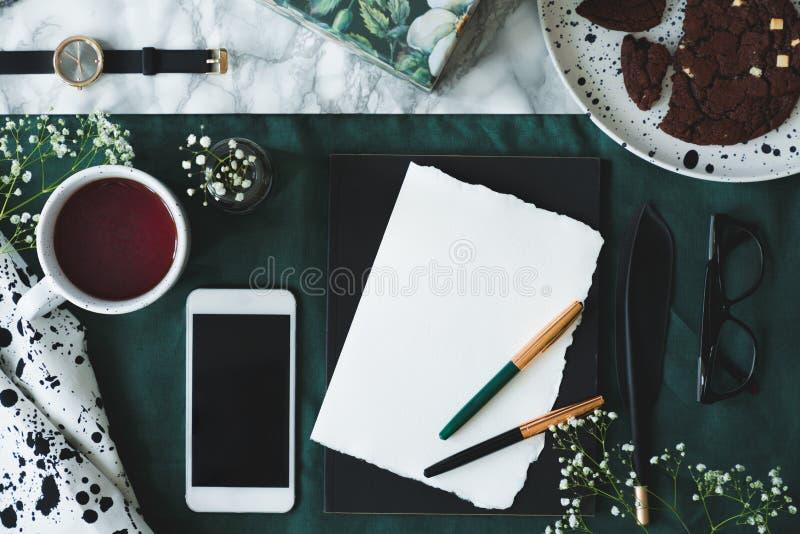 大理石样式桌有空的纸顶视图与两翎毛钢笔的,玻璃、杯子用茶和大模型打电话 免版税库存图片