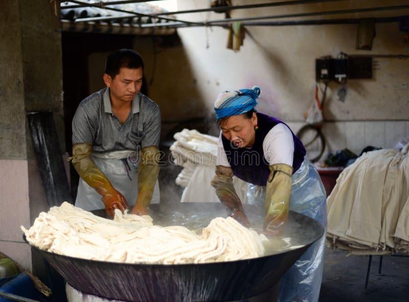 大理,中国8月16日2013年:做蜡染布的人们 库存图片