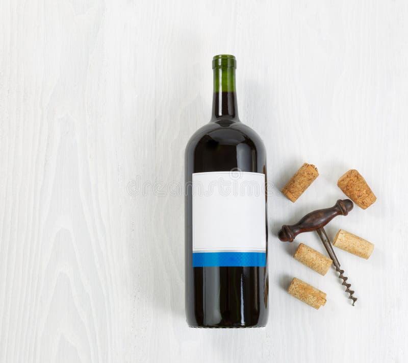 大瓶与古色古香的拔塞螺旋和老黄柏的红葡萄酒 库存照片